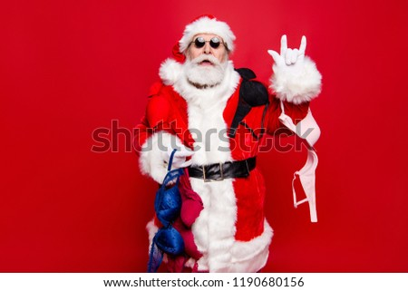 December noel winter wish Christmastime. Mature aged stylish trendy grandfather Santa spectacles tradition headwear costume white beard show rock n roll heavy metal sign isolated red background #1190680156