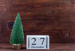December 27 on the calendar.Calendar with a small Christmas tree on a wooden background. Winter. Empty space for text.