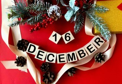 December 16 on wooden cubes.Near fir branches, cones, ribbon, gift box on a red background.Winter.Calendar for December