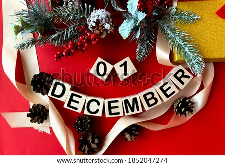 Photo of  December 1 on wooden cubes.Near fir branches, cones, ribbon, gift box on a red background.Winter.Calendar for December