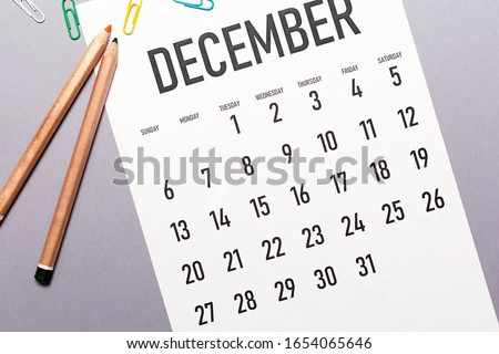 Photo of  December 2020 simple calendar with office supplies and copy space
