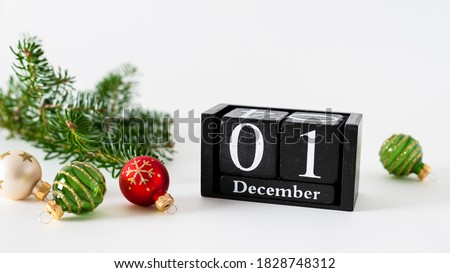 Photo of  December 1st. Day 1 of december month, calendar with christmas balls decoration and fir branches on white background. Winter time. New year, hello winter holidays concept. Horizontal