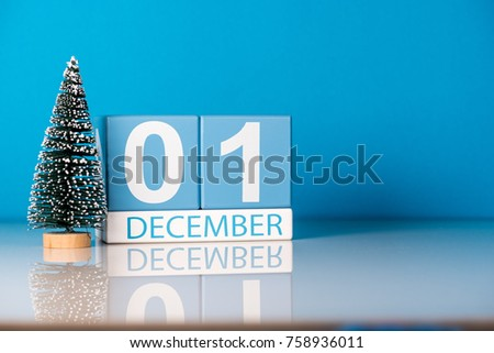 December 1st. Day 1 of december month, calendar with little christmas tree on blue background. Winter time. Empty space for text. New year concept