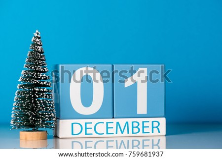 December 1st. Day 1 of december month, calendar with little christmas tree on blue background. Winter time. New year concept