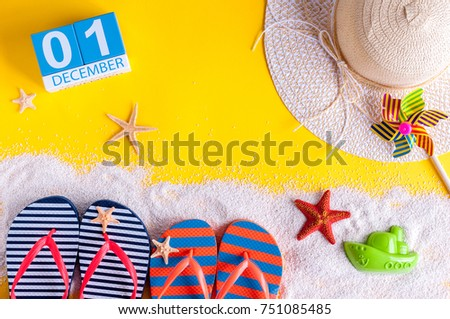 December 1st. Image of december 1 calendar with summer beach accessories and traveler outfit on background. Winter like Summer vacation concept