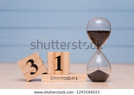 December 31st set on wooden calendar and red alarm clock with blue background. Clock show five minutes to midnight #1243186021