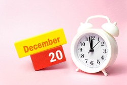 December 20th. Day 20 of month, Calendar date. White alarm clock on pastel pink background. Winter month, day of the year concept