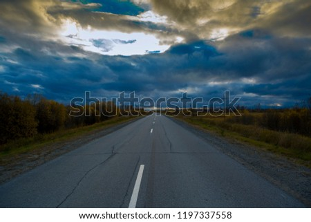 Deciduous autumn forest grows along an asphalt road with a discontinuous divided strip against the stormy sky