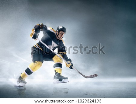 Decisive throw of the puck and goal. Ice hockey player in action on ice. Male professional athlete swinging his stick before a decisive blow. Tension and rage. Sports emotions. Motion and movement.