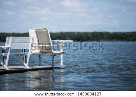 deck chairs and table floating on calm peaceful serene water #1450084127