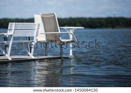 deck chairs and table floating on calm peaceful serene water #1450084130