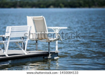 deck chairs and table floating on calm peaceful serene water #1450084133