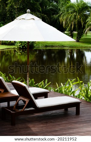 Deck chairs and umbrellas next to a lake.