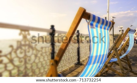 Deck chairs billowing in breeze on Brighton Pier, Brighton beach, Sussex southern England