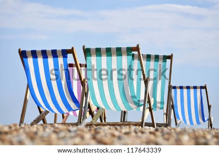 Deck chairs on Brighton beach in summer, England, UK