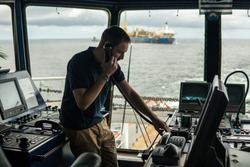 Deck navigation officer on the navigation bridge. He speaks by VHF radio, GMDSS Watchkeeping, collision prevention at sea. COLREG