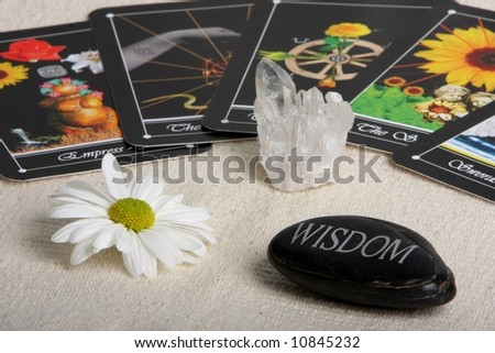 deck of tarot cards spread on table with crystal flower and wisdom stone