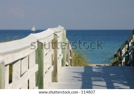 deck to the beach with sailboat on the ocean