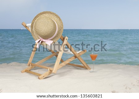 deckchair with summer hat  at the beach
