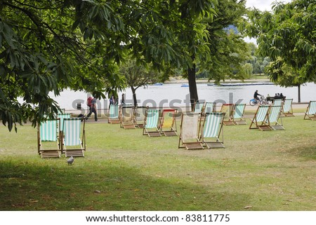 Deckchairs for hire by The Serpentine boating lake in Hyde Park. Westminster. London. England.