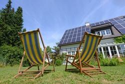 Deckchairs in garden of solar paneled house