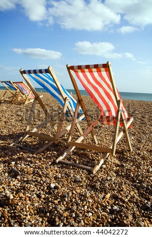 deckchairs on beach on windy day in brighton. pebble coastline or seashore in england with outdoor sun relaxing chair furniture