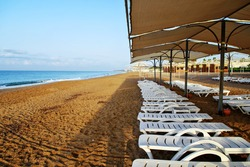 Deckchairs stand in a row on the beach, without people, early morning, concept trip, vacation