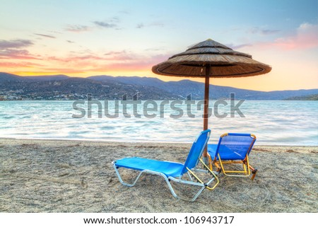 Deckchairs with parasol at Mirabello Bay at sunset, Greece