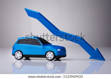 Declining Arrow Over Blue Car Against Gray Background