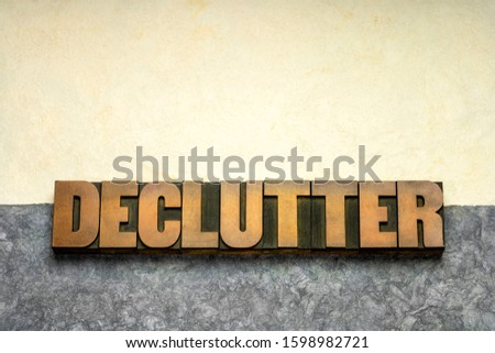 declutter word in vintage letterpress wood type against handmade textured amate paper, simplicity, minimalism and lifestyle concept