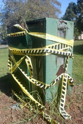 Decommissioned and damaged utility box wrapped in caution tape