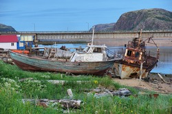 Decommissioned fishing boats on the shores of the Barents Sea in the village of Teriberka with a mountain in the background.