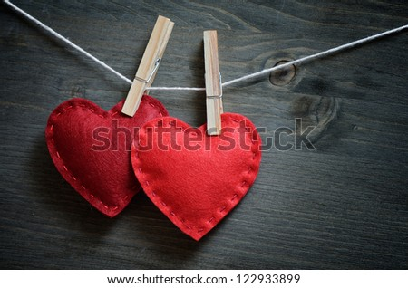 Decor for Valentine's Day. Two hearts made ??of red felt on clothespins - stock photo
