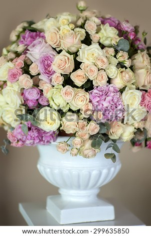 Decorate wedding bouquet of fresh beautiful flowers of roses and peony white pink violet purple yellow lilac and orange colours in big vase on beige background, vertical picture