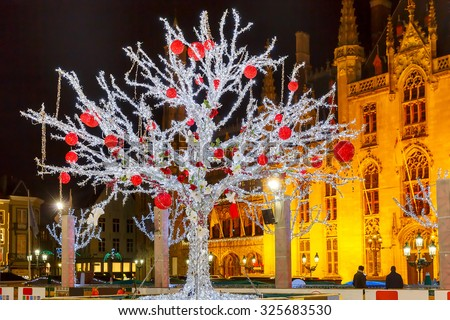 Decorated and illuminated Christmas tree on the rink in front of Province Court at Market Place in the center of Bruges at night, Belgium