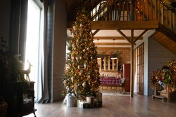 Decorated apartment with festive lights, Christmas tree and gift boxes under in living room, modern dining room with served table, empty house prepared for family New Year celebration, winter holiday