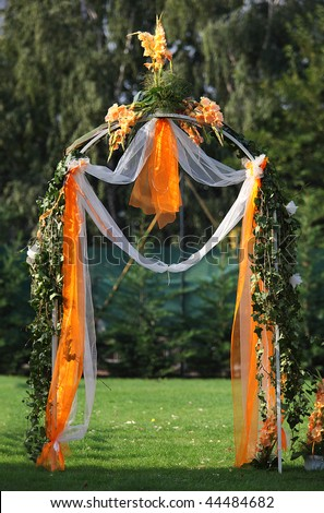 Decorated archway for wedding ceremony with colorful flowers and ribbons