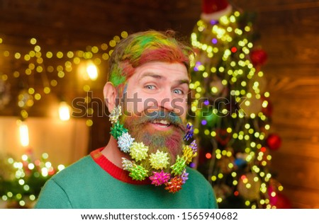 Decorated beard. Merry Christmas and happy new year. Smiling bearded man with decorated beard. Christmas beard decorations. New year party. Bearded man with decorated beard. Christmas decorations.