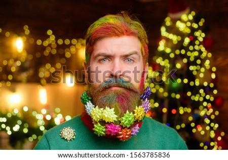 Decorated beard. Serious bearded man with decorated beard. Christmas beard decorations. New year party. Bearded man with decorated beard. Christmas decoration. Christmas holidays. Winter holidays