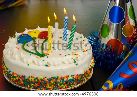 Decorated Birthday cake with candles and party hats