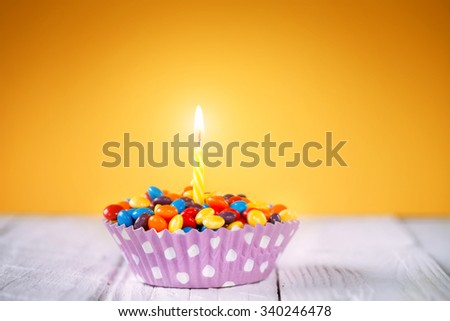 Decorated Birthday cupcake with one lit candle and colorful candies on yellow background Happy birthday card.