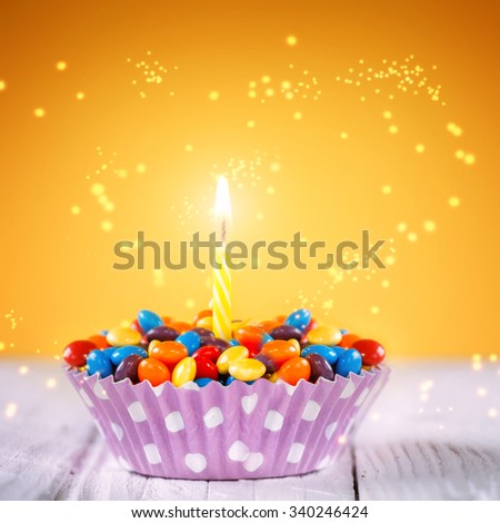 Decorated Birthday cupcake with one lit candle and colorful candies on yellow background. Holidays greeting card