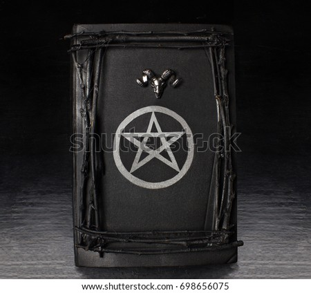 Decorated black magic book with pentagram symbol and silver ram's head on it. Stock photo ©