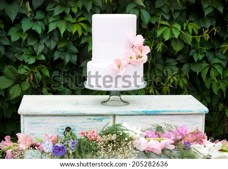 Decorated cake with flowers on green floral background
