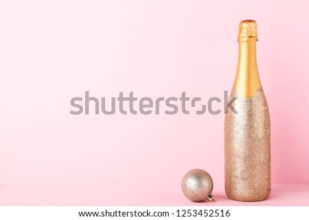 Decorated champagne bottle with christmas bauble on pink background #1253452516