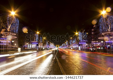 Decorated Champs-Elysees street with light trails at night in Paris, France