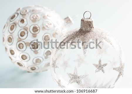 Decorated Christmas ornaments on a soft blue background.