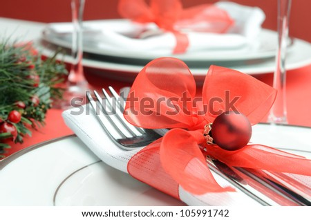 Decorated christmas table setting in festive red white colours, napkin cutlery tied with organza ribbon and holiday bauble