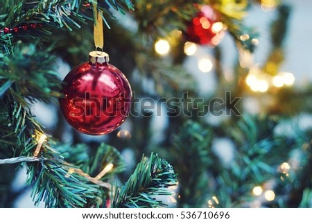 Decorated Christmas tree closeup. Red and golden balls and illuminated garland with flashlights. New Year baubles macro photo with bokeh. Winter holiday light decoration