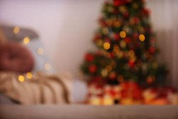 Decorated Christmas tree in soft yellow lights with bokeh effect background. Lofty apartment with traditional new year holiday decoration, intimate lighting. Close up, copy space.
